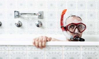 Man with snorkelling gear in the bath