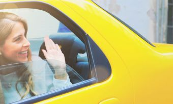 Girl Waving From Inside a Yellow Taxi
